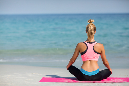 Rear view of woman meditating while sitting on shore at beach