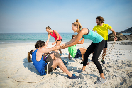 bonding rope: Friends helping man and woman while playing tug of war at beach