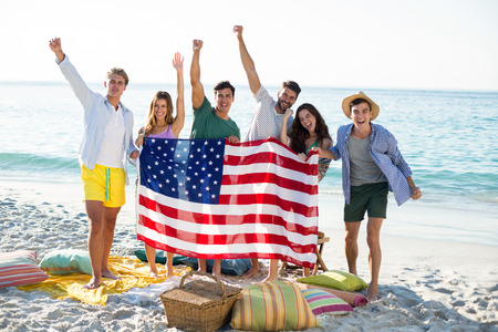 Happy friends holding American flag while standing on shore at beach Stock Photo