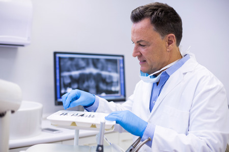 scaler: Attentive dentist checking tools in dental clinic Stock Photo