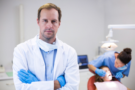 sickle: Portrait of dentist standing with arms crossed in clinic Stock Photo