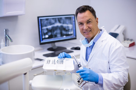 scaler: Portrait of smiling dentist holding dental hand piece in clinic