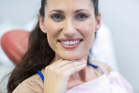 Portrait of smiling female patient sitting on dentist chair at dental clinic Stock Photo