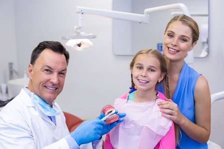Portrait of dentist with young patient and his mother at dental clinic