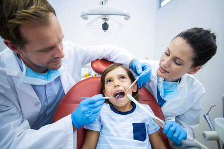 scaler: Attentive dentists examining young patient in dental clinic