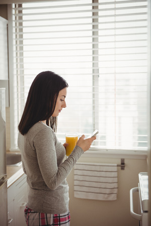 Side view of woman using smart phone while standing against window at home