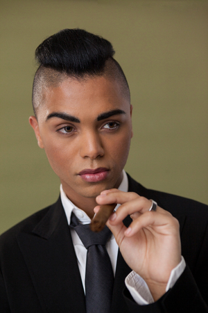 Close up of transgender woman holding cigarette on green background Banco de Imagens