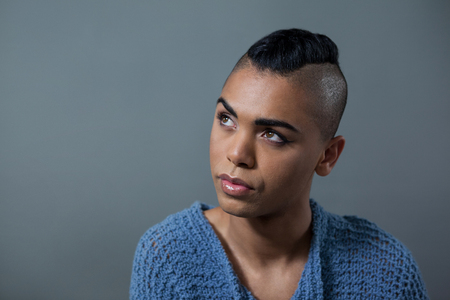 Transgender woman looking away while standing against gray background Stock Photo - 76068638