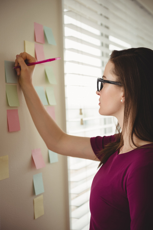 Woman  writing on sticky note by window at home