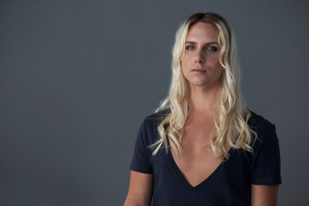 Portrait of transgender woman with blond hair standing over gray background 写真素材