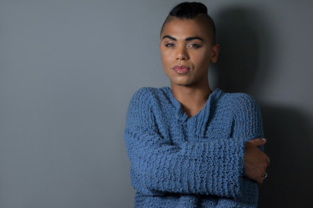 Portrait of confident transgender embracing against gray background 스톡 콘텐츠