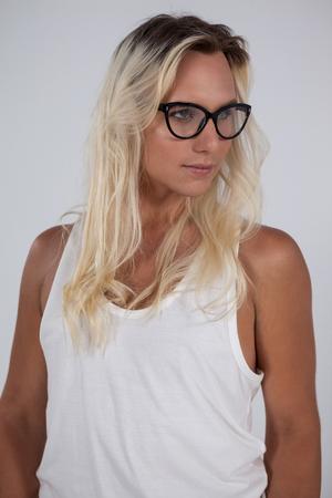 5d8a13f16cce94  76068932 - Transgender vrouw draagt   bril tegen een groene achtergrond