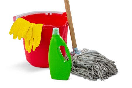 Close up of chemical bottle and mop with bucket against white background