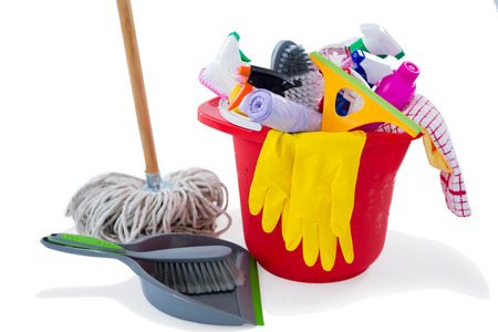 Mop and dustpan by cleaning products in bucket against white background