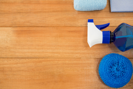 Overhead view of blue spray bottle and sponge on wooden table