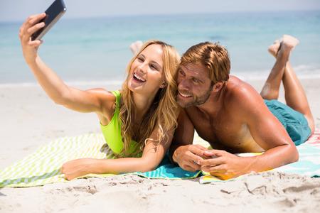 comunicacion oral: Pareja sonriendo mientras toma selfie en la playa durante el día soleado