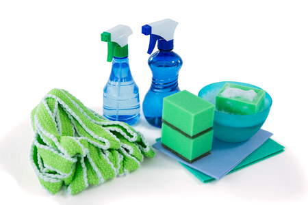 Close up of spray bottles with bowl and sponges against white background