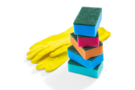 Close up of colorful sponges and gloves against white background Imagens