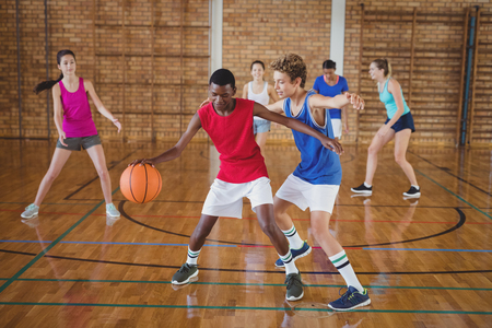 Determined high school kids playing basketball in the court Foto de archivo