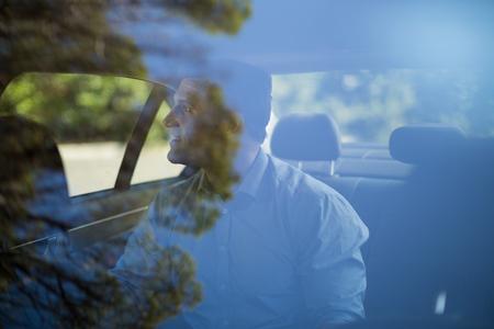 Man sitting on back seat seen through car windshield Stock Photo