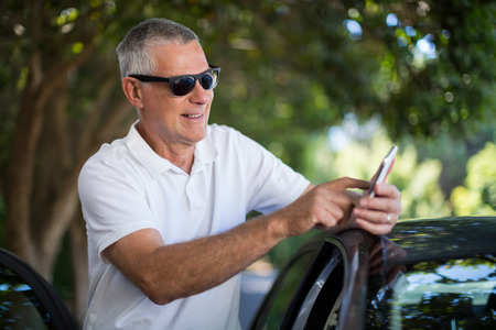 Smiling senior man using smart phone while standing by car
