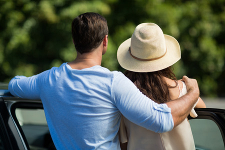 Rear view of young couple leaning on car door Stock Photo