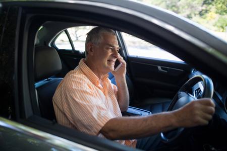 Senior man talking on phone while sitting in car