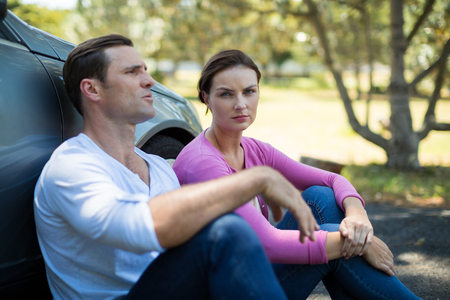 Tired couple sitting by breakdown car on road