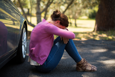 Sad woman sitting by breakdown car
