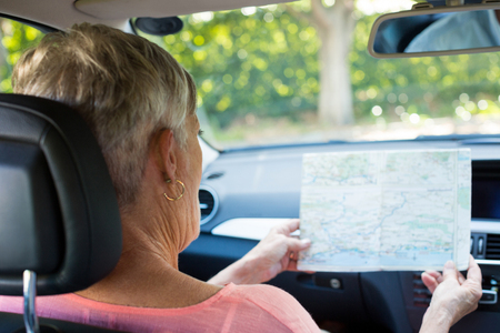 Rear view of senior woman reading map while sitting in car