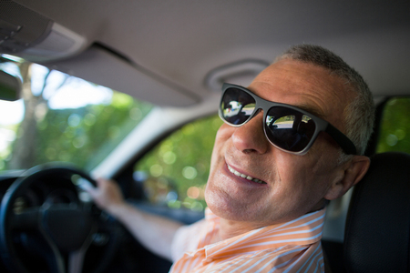 Portrait of smiling senior man wearing sunglasses while traveling in car