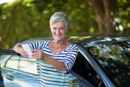 Portrait of senior woman holding phone while leaning on car door