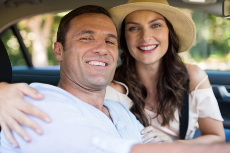 Portrait of smiling young couple sitting in car