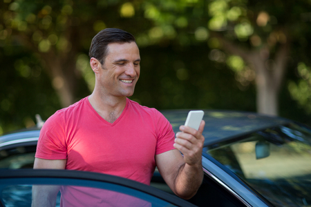 Smiling man using mobile phone by car