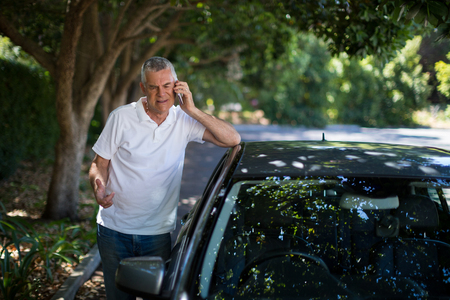 Senior man talking on phone while standing by car