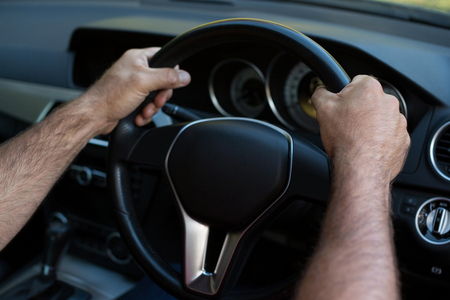 Cropped hands of person driving car Stock Photo
