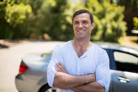 Portrait of man with arms crossed standing by car