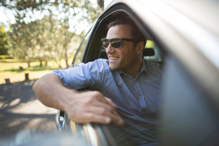 Smiling young man sitting in car Stock Photo