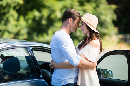 Happy young couple embracing by car on sunny day