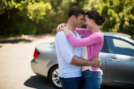 Young couple embracing by car on sunny day