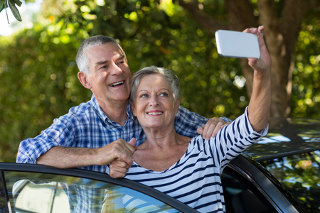 Happy senior couple taking selfie by car