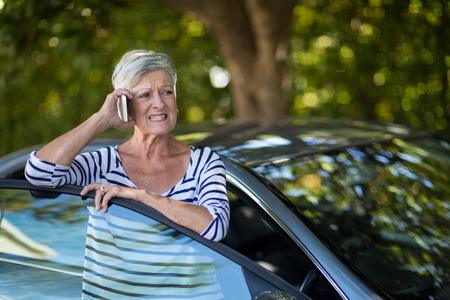 Annoyed senior woman talking on phone by car