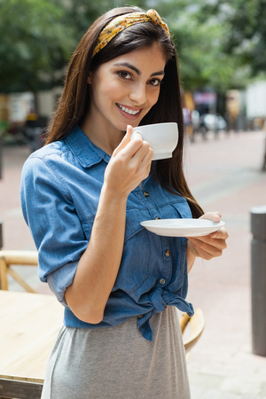 Portrait of woman drinking coffee while standing at cafe shop