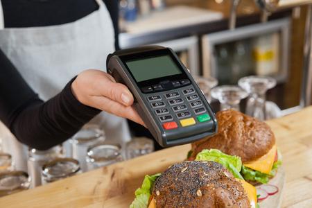 Close up of owner holding credit card reader at cafe shop