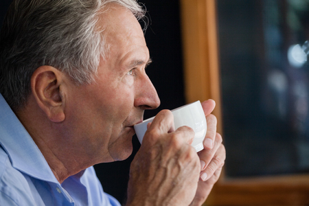 Close up of senior man drinking coffee at cafe shop Stock Photo