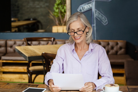 the sixties: Smiling senior womanb holding tablet computer while sitting at table in cafe shop Stock Photo