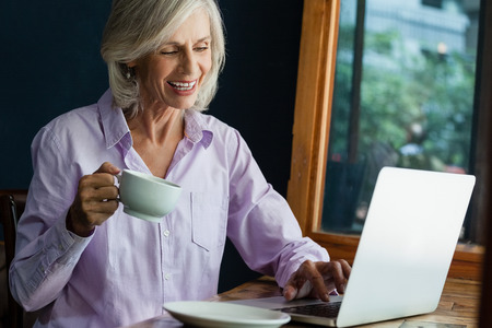 hapiness: Smiling senior woman drinking coffee while working on laptop at table in cafe shop