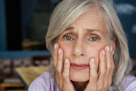 Portrait of worried senior woman in cafe shop Stock Photo