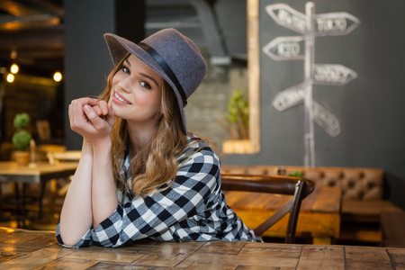 Portrait of smiling young woman leaning at table in cafe
