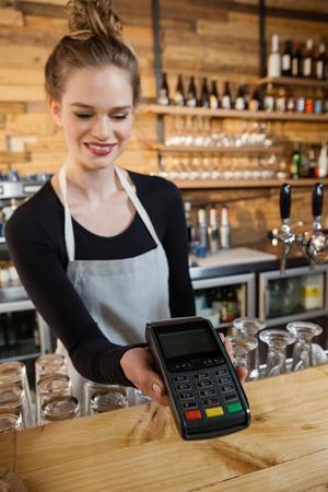 Smiling woman holding credit card reader at cafe shop
